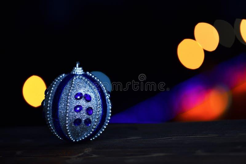 新年假日xmas装饰五颜六色的玩具或球与defocused bokeh光在五颜六色的背景,拷贝spac 免版税库存图片