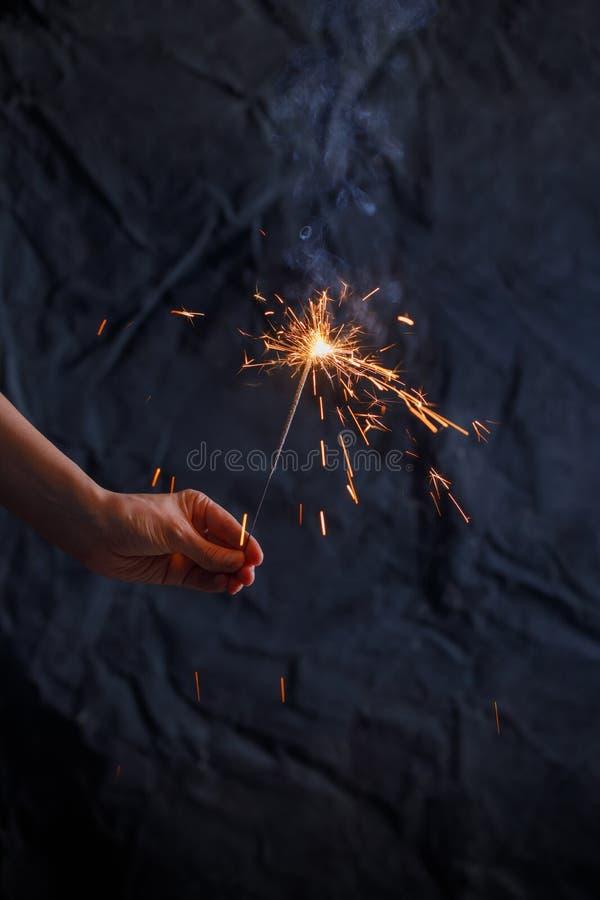 新年党灼烧的闪烁发光物特写镜头在黑背景的女性手上 妇女拿着发光的假日闪耀的手烟花, 免版税图库摄影