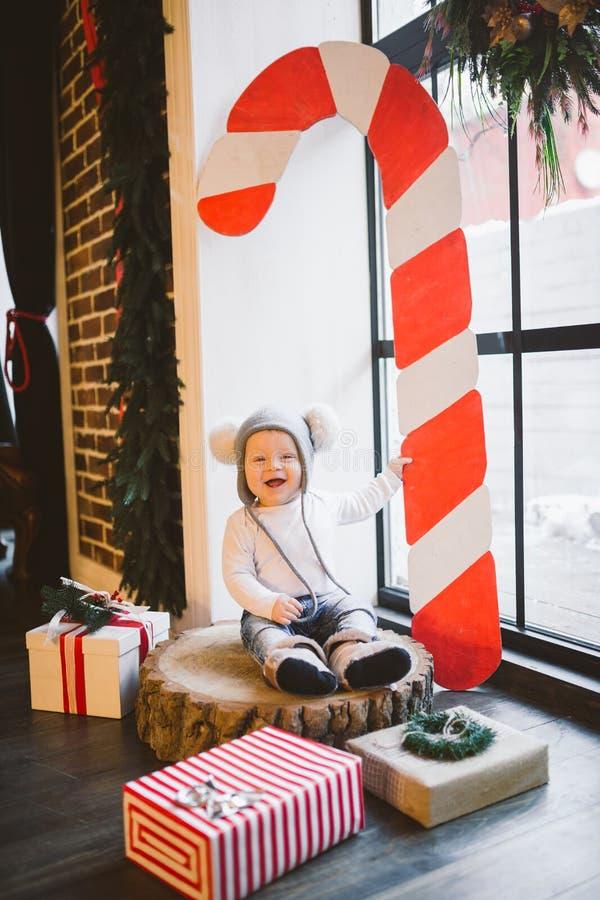 新年和圣诞节假日题材白种人儿童男孩1岁坐树桩击倒的树在一个滑稽的帽子的窗口附近 免版税库存图片