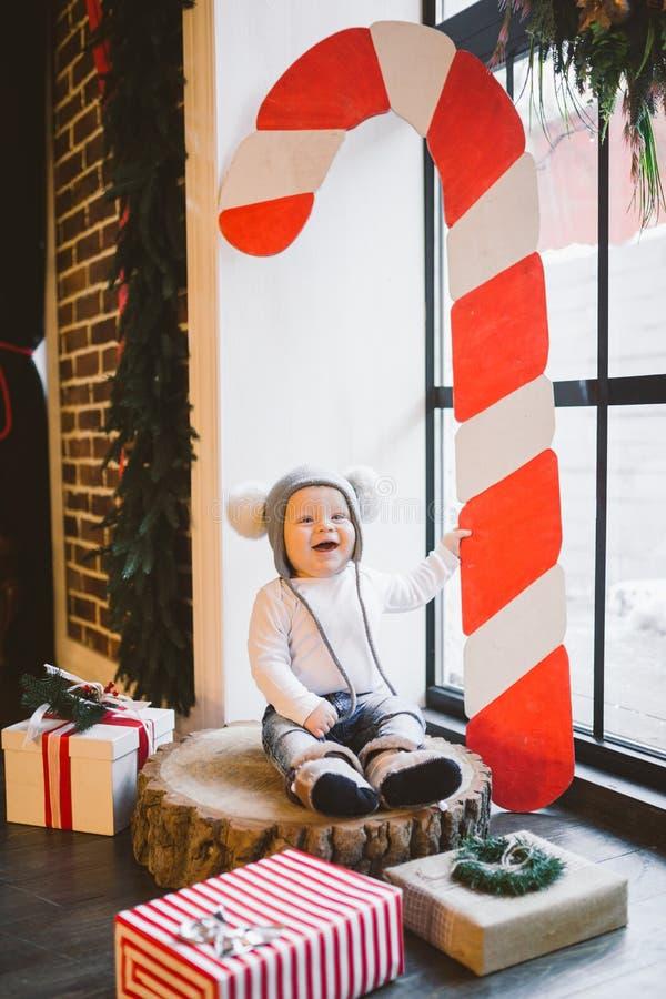 新年和圣诞节假日题材白种人儿童男孩1岁坐树桩击倒的树在一个滑稽的帽子的窗口附近 库存图片