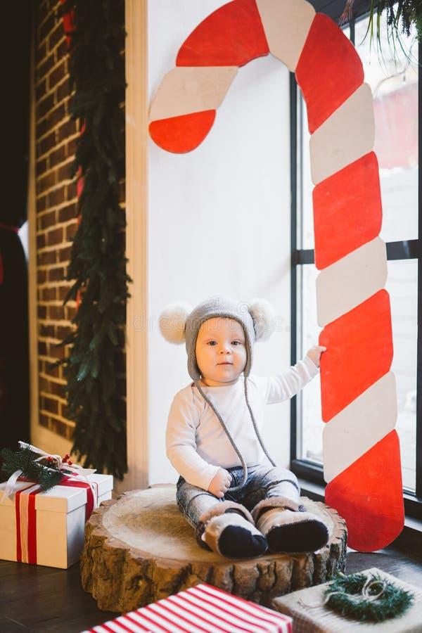 新年和圣诞节假日题材白种人儿童男孩1岁坐树桩击倒的树在一个滑稽的帽子的窗口附近 免版税库存照片