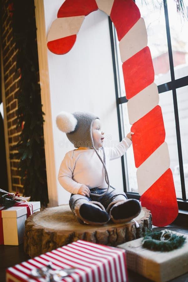 新年和圣诞节假日题材白种人儿童男孩1岁坐树桩击倒的树在一个滑稽的帽子的窗口附近 库存照片