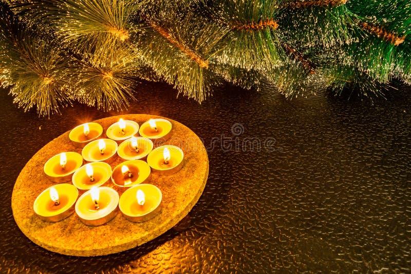 新年和圣诞节,在黑背景的绿色人为杉木根据蜡蜡烛 黄色温暖的亲切接触,我 免版税库存图片