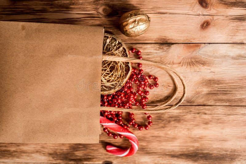 新年圣诞礼物 舱内甲板被放置的顶视图Xmas假日 庆祝手工制造礼物工艺组装 金黄球、坚果和红色 库存图片