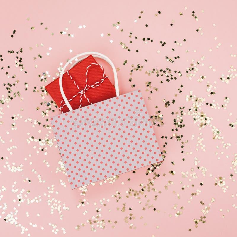 新年圣诞节销售顶视图平的被放置的购物带来有最小礼物当前金黄星五彩纸屑千福年的桃红色的背景 库存图片