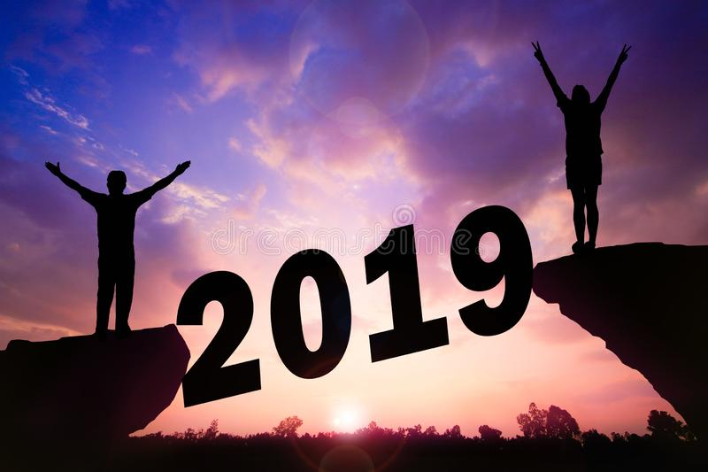 新年好剪影日落背景 在峭壁的一个男人和妇女身分 图库摄影