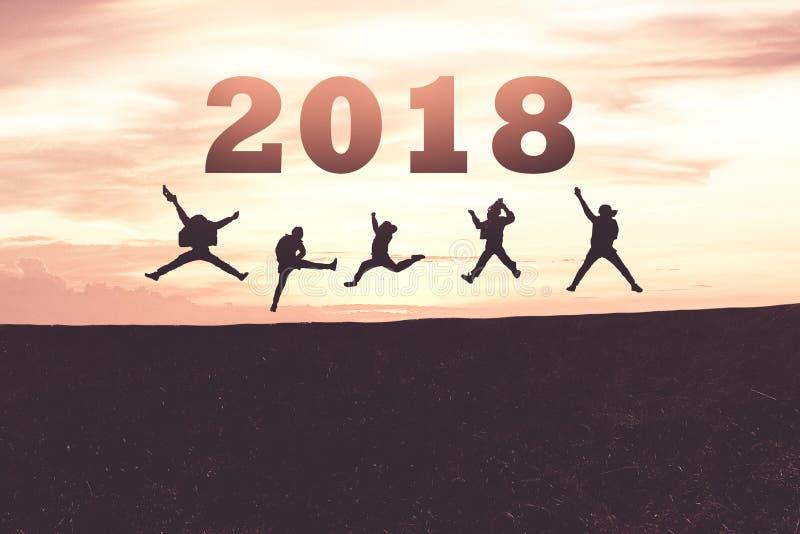 新年好卡片2018年 跳跃在山小山的少年剪影有意想不到的日落天空背景 库存照片