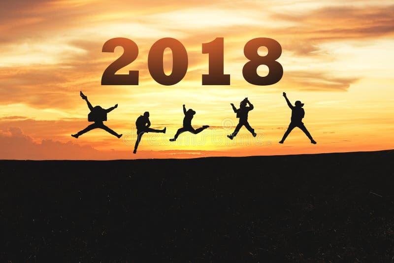 新年好卡片2018年 跳跃在山小山的少年剪影有意想不到的日落天空背景 免版税图库摄影