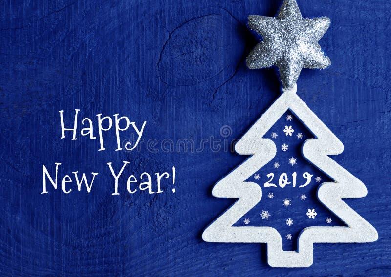 新年好贺卡 与2019数字的白色圣诞节快乐树在深蓝木背景 免版税库存图片