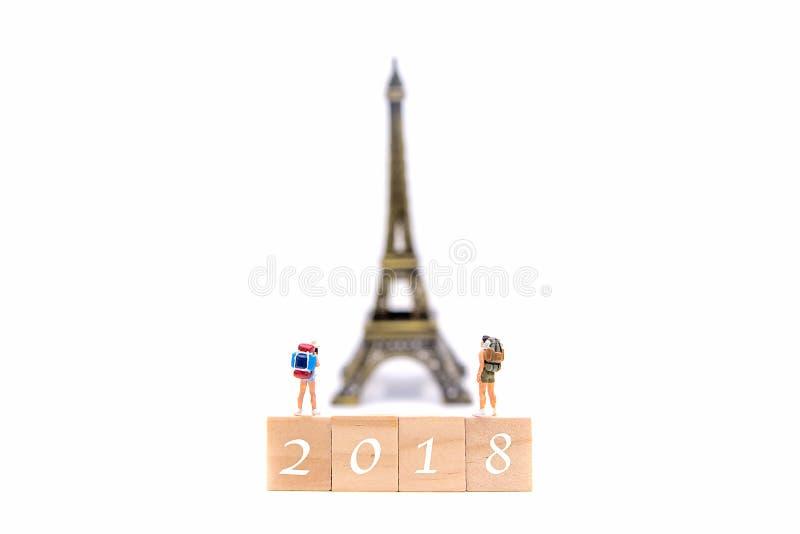 新年好2018年 微型小组远足者和旅客挑运在黄木樨草地图的身分在法国和aroun的旅行的艾菲尔铁塔 免版税库存图片