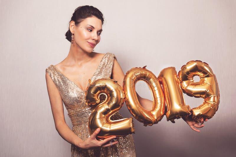 新年好 有气球的美女庆祝除夕党的 明亮的发光的礼服的微笑的女孩与 库存照片