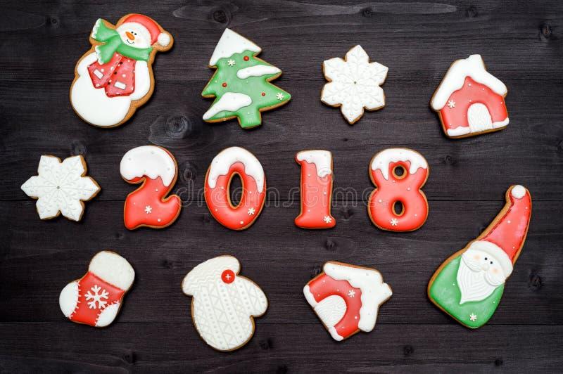 新年好2018标志标志和红色和白色姜饼曲奇饼在黑暗的木背景 顶视图,平的位置 免版税库存图片