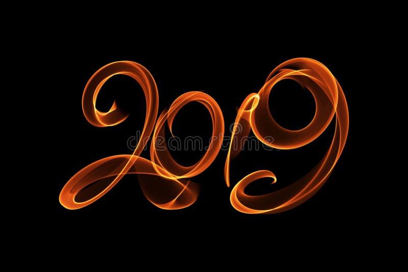 新年好2019隔绝了数字在上写字写与火火焰或烟在黑背景 免版税图库摄影