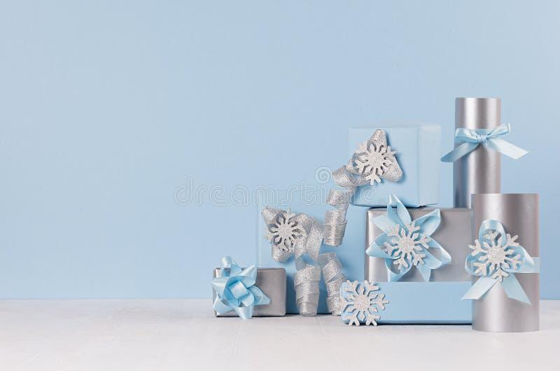 新年庆祝在蓝色淡色和银的欢乐在白色木头的礼物盒金属与发光的丝带和弓 库存照片