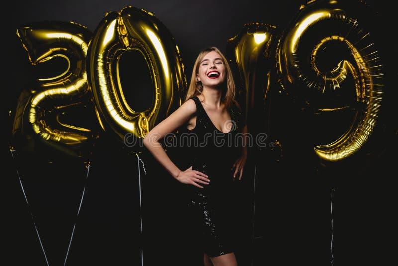 新年度 有气球的妇女庆祝在党的 美丽的微笑的女孩画象发光的礼服投掷的五彩纸屑的 免版税库存照片
