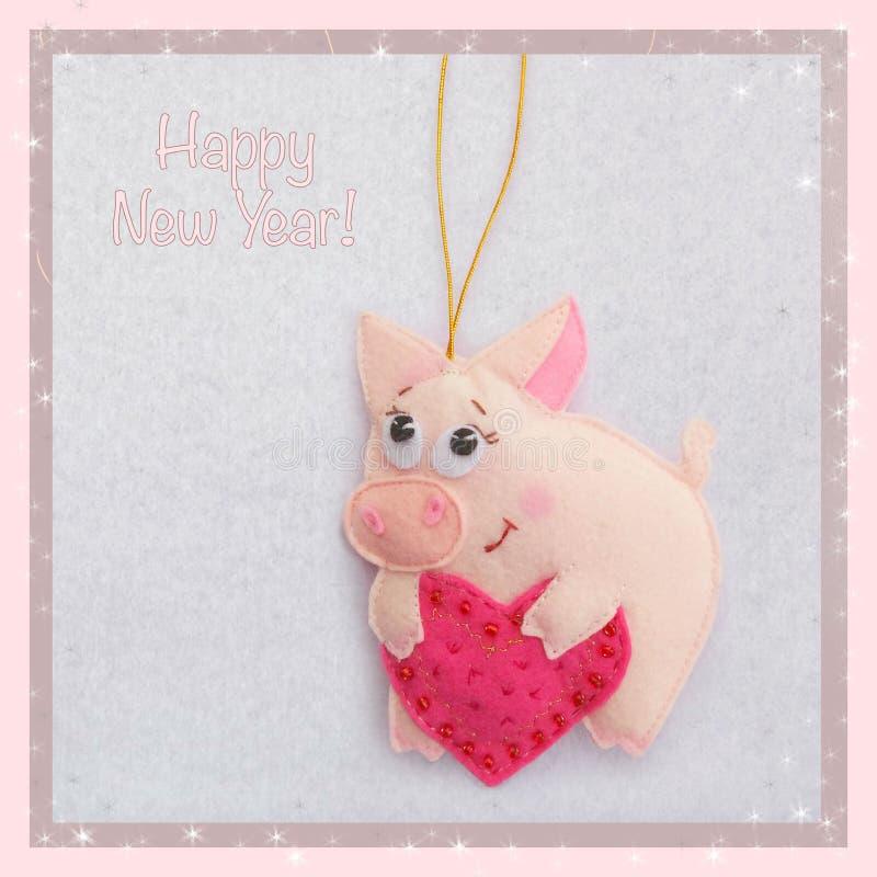 新年度 软的玩具由毛毡制成 逗人喜爱的猪 小猪拿着心脏 圣诞树装饰 年的标志 2019年 库存图片