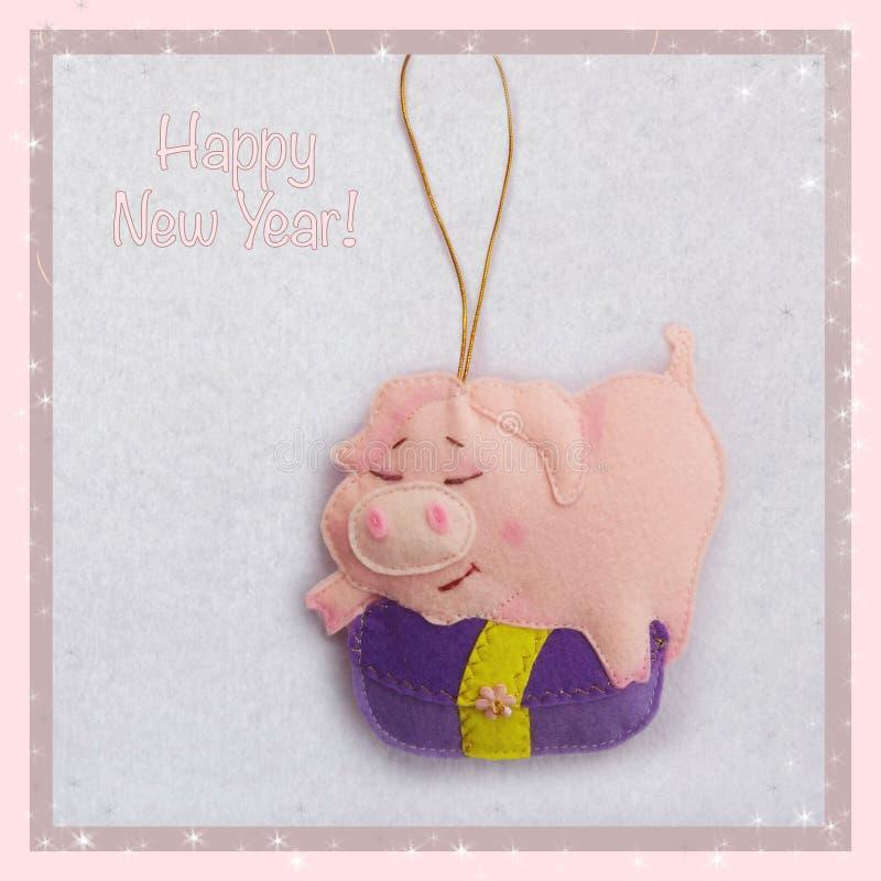 新年度 软的玩具由毛毡制成 逗人喜爱的猪 贪心拿着礼物 圣诞树装饰 年的标志 2019年 库存图片