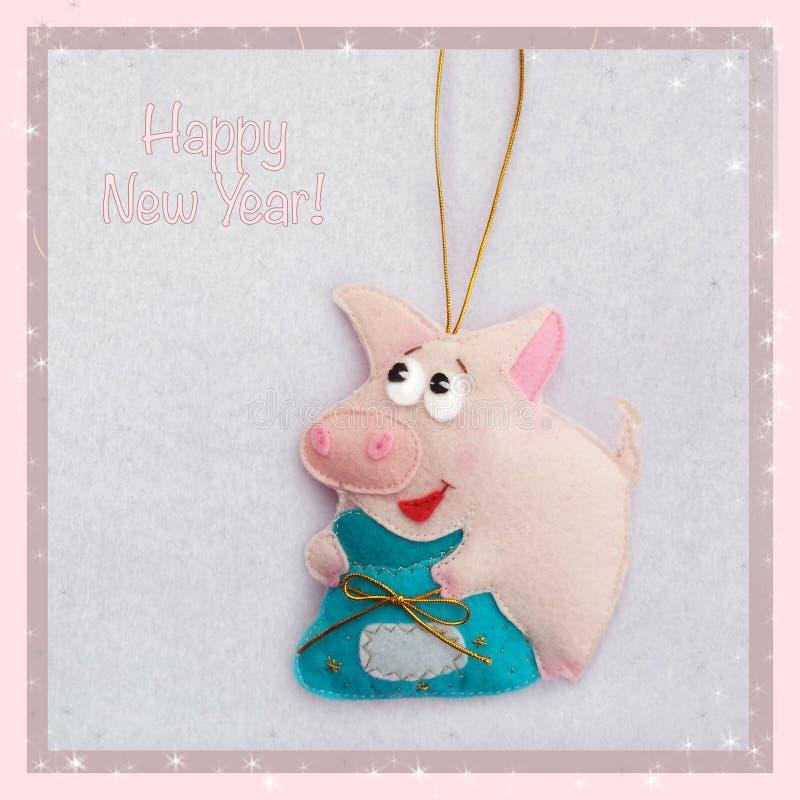 新年度 软的玩具由毛毡制成 逗人喜爱的猪 贪心拿着袋子礼物 圣诞树装饰 年的标志 2019年 库存图片