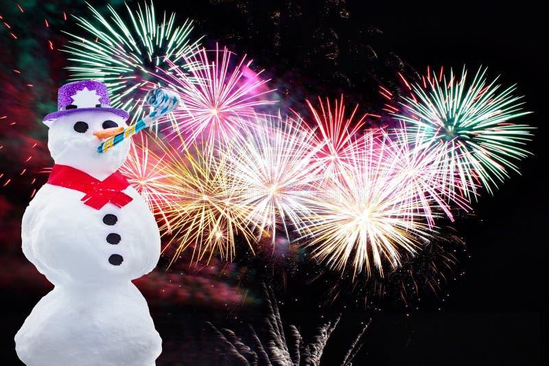 新年快乐在与五颜六色的烟花的黑背景隔绝的一个滑稽的党雪人 库存图片