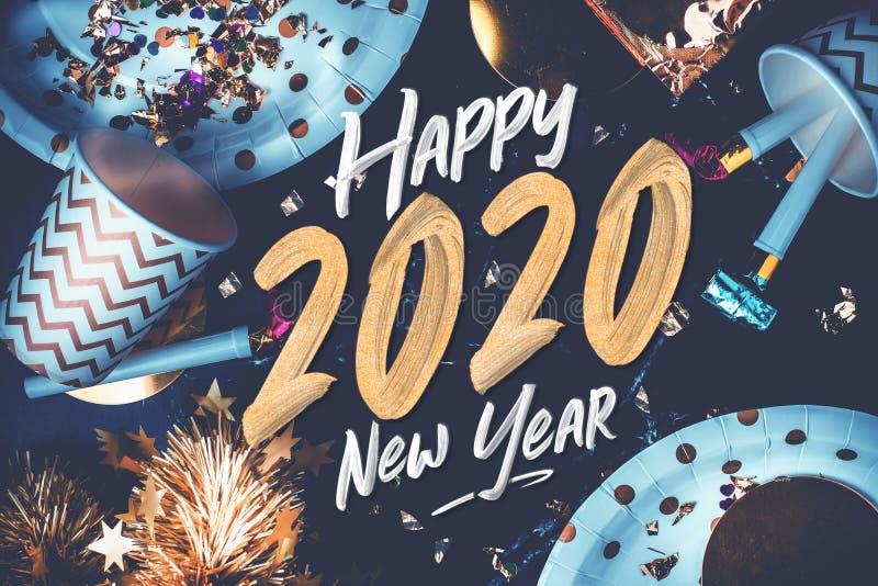 2020新年快乐手刷子在大理石桌上的storke字体与党杯子,党吹风机,闪亮金属片,五彩纸屑 乐趣庆祝节日晚会 免版税库存照片