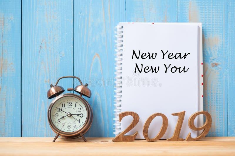 2019新年快乐新您在笔记本、减速火箭的闹钟和木数字发短信在桌和拷贝空间上 免版税库存图片