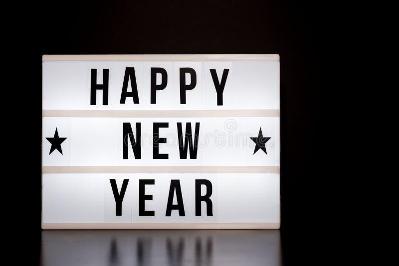 新年快乐标志-戏院在灯箱&黑背景的样式字法 库存图片