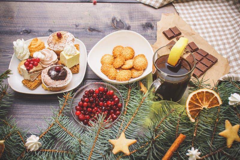 新年快乐用姜饼星、肉桂条、干橙色切片和蛋白甜饼峰顶装饰的冷杉分支,明亮 库存照片