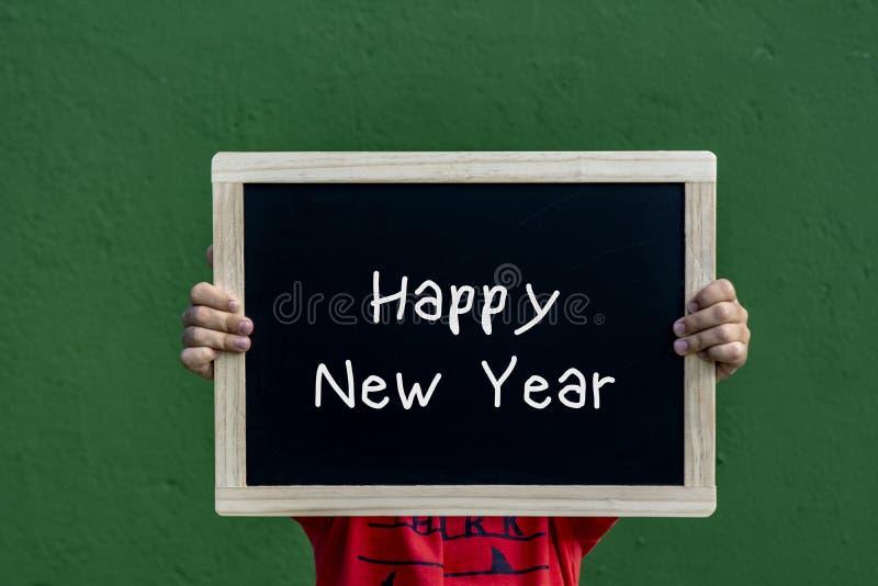 新年快乐由的书面黑板孩子 免版税图库摄影