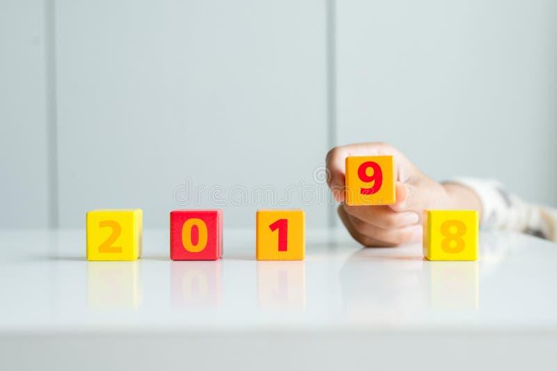 新年快乐2018变动到2019年,改变或投入立方体木刻的手妇女的概念 免版税库存图片