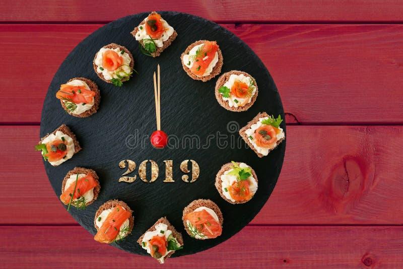 新年快乐2019年!显示12点,与熏制鲑鱼点心的创造性的食物想法的时钟 免版税库存图片