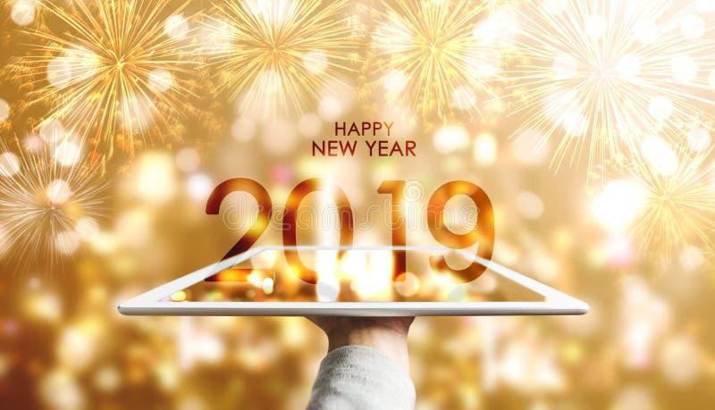 新年快乐2019年,拿着数字片剂有豪华金子Bokeh烟花背景的手 库存图片
