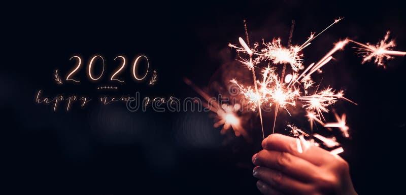 新年快乐2020文本用举行燃烧的闪烁发光物烟花疾风有在黑bokeh背景的手在晚上,假日 免版税库存图片