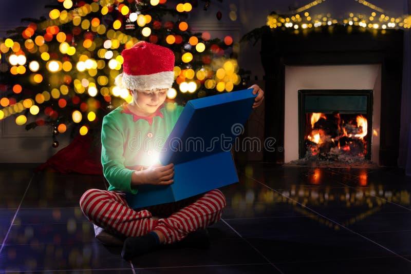 新年树木和壁炉附近的男孩开放礼物 免版税图库摄影