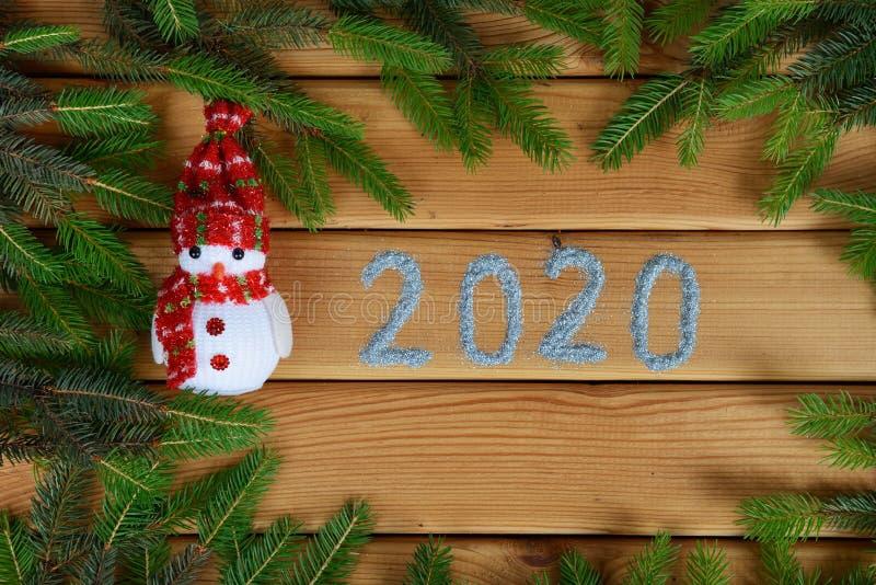 新年树枝、雪人和手工制造2020年题字 免版税图库摄影