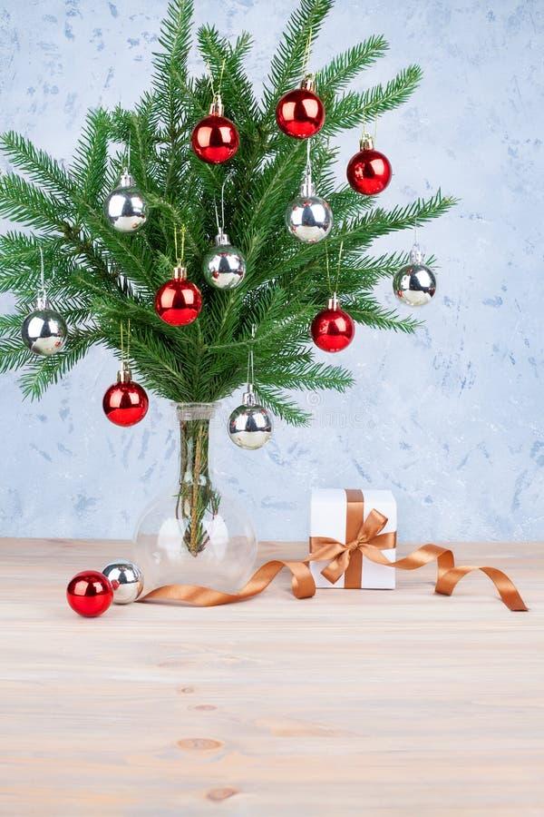 新年欢乐贺卡银色设计、的圣诞装饰和在绿色冷杉分支的红色球在玻璃花瓶,礼物盒 图库摄影