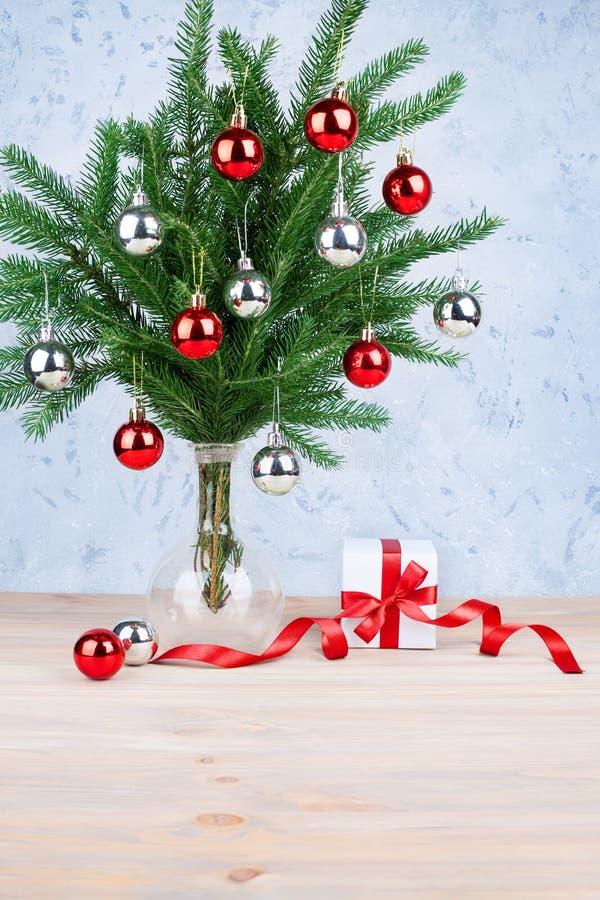 新年欢乐贺卡银色设计、的圣诞装饰和在绿色杉木分支的红色球在玻璃花瓶,礼物盒 免版税库存图片