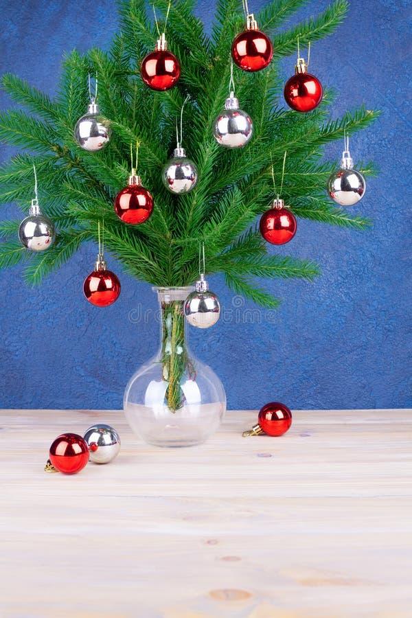 新年欢乐银色贺卡、的圣诞装饰和在绿色杉木分支的红色球在木桌上的玻璃花瓶 库存照片