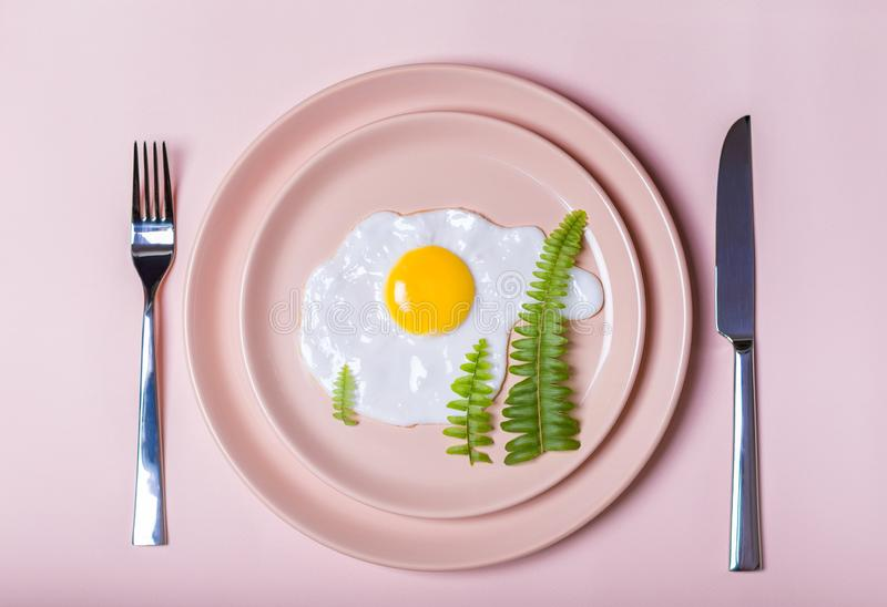 新年的早餐:在米黄板材的荷包蛋 象圣诞树的绿色叶子 叉子和刀子 在视图之上 图库摄影