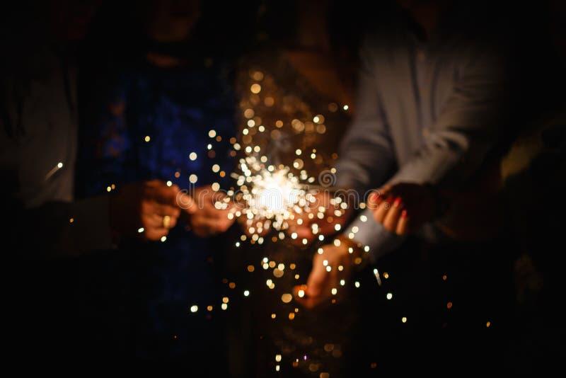 新年聚会燃烧的闪烁发光物特写镜头在黑背景的手上 握发光的假日闪耀的手的人公司  图库摄影