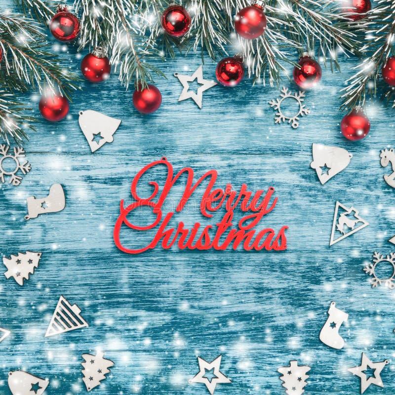 新年贺卡,方形的形状,在天蓝色的背景 与红色球的冷杉分支 木圆木玩具 免版税库存照片