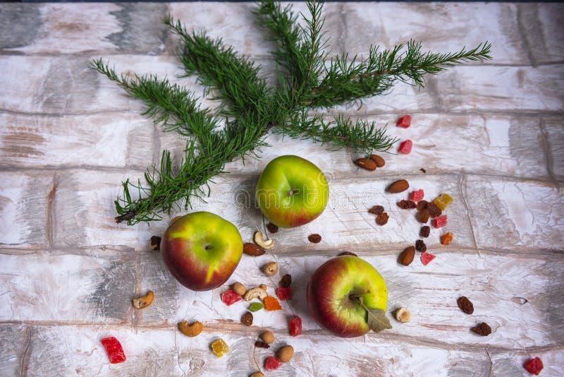 新年贺卡,苹果,落叶松属小树枝在仿效砌的背景的 免版税库存图片