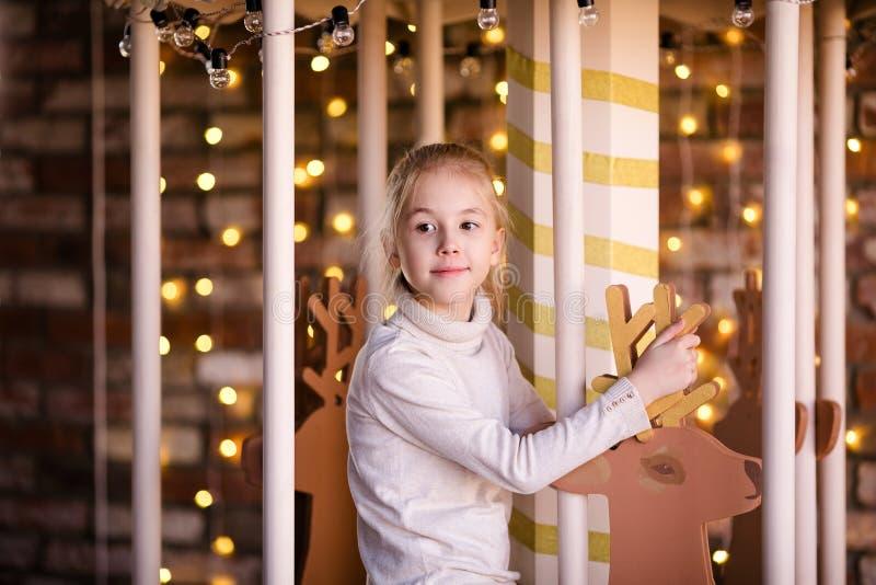 新年转盘的好白肤金发的女孩有木鹿和明亮的光的 库存照片