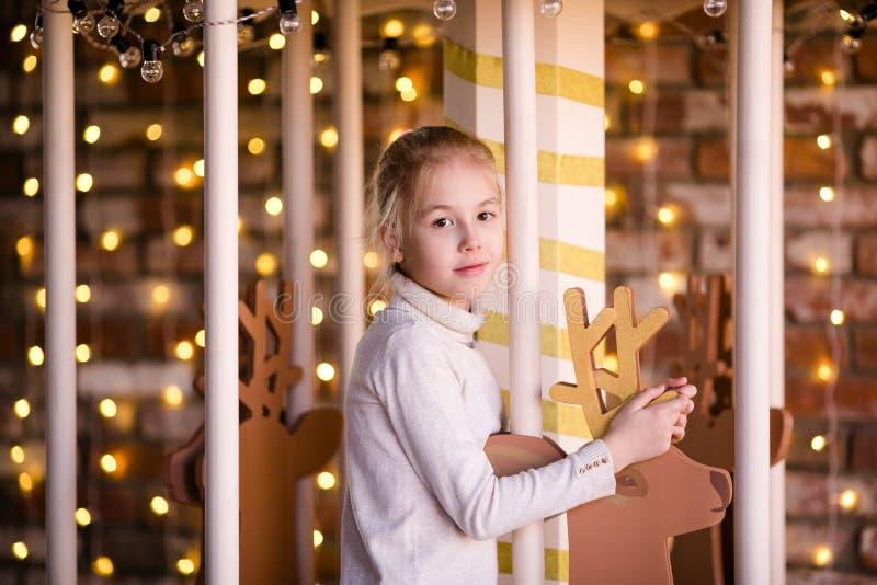 新年转盘的好白肤金发的女孩有木鹿和明亮的光的 免版税库存图片