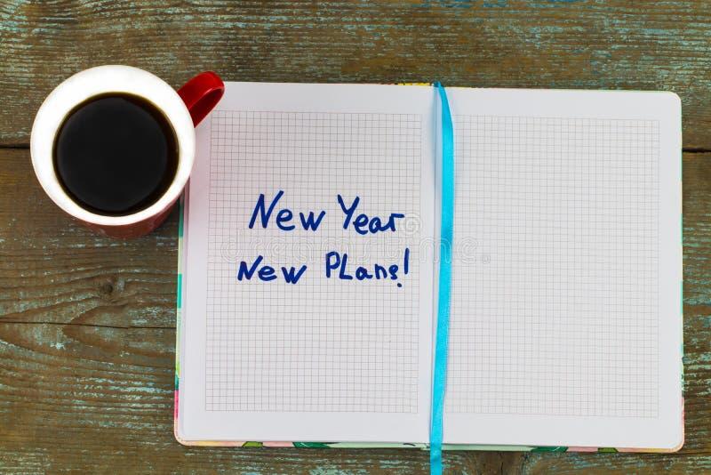 `新年,在笔记薄的新的计划`文本,与在木桌上的咖啡和笔-企业和财务概念 库存图片