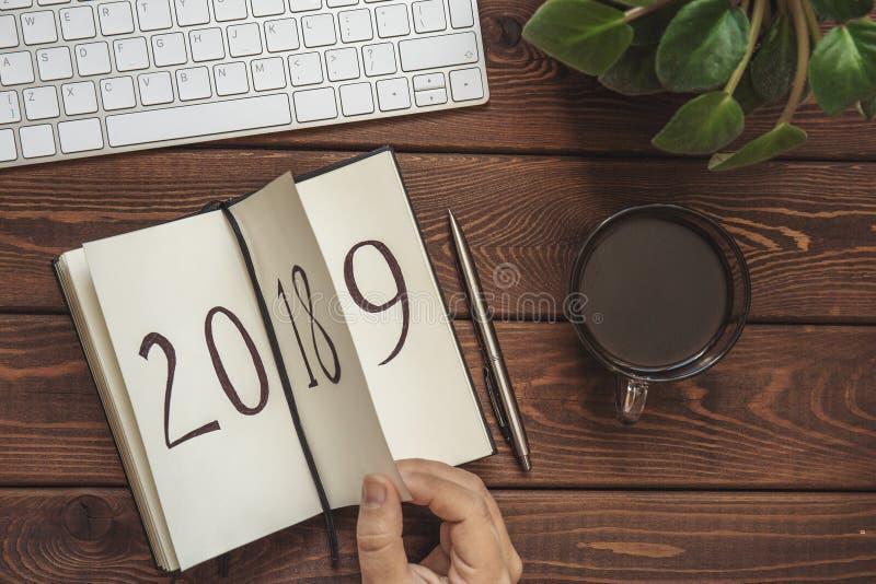 新年2019年是以后的概念 女性手翻转在木桌上的笔记薄板料 2018年转动, 2019年打开,顶视图 免版税库存照片