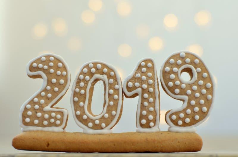 新年2019年 在一个木板的姜饼形象 在背景的圣诞灯 问候新年度 适当作为backg 库存图片