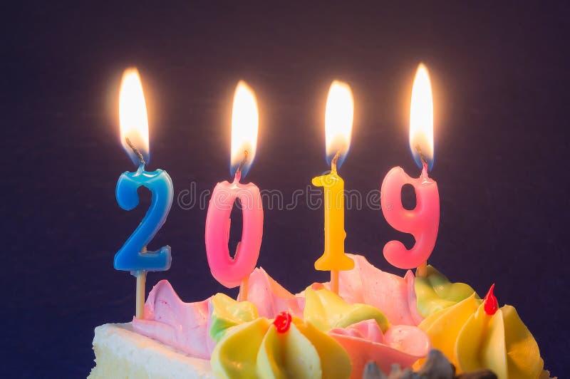 新年2019年 在蛋糕特写镜头的燃烧的欢乐蜡烛 免版税库存图片