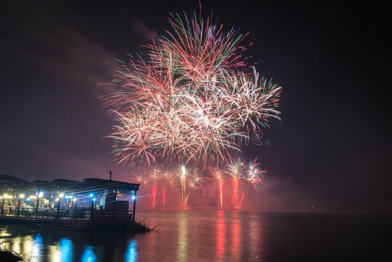 新年` s伊芙烟花从与反射的水发射了 库存图片