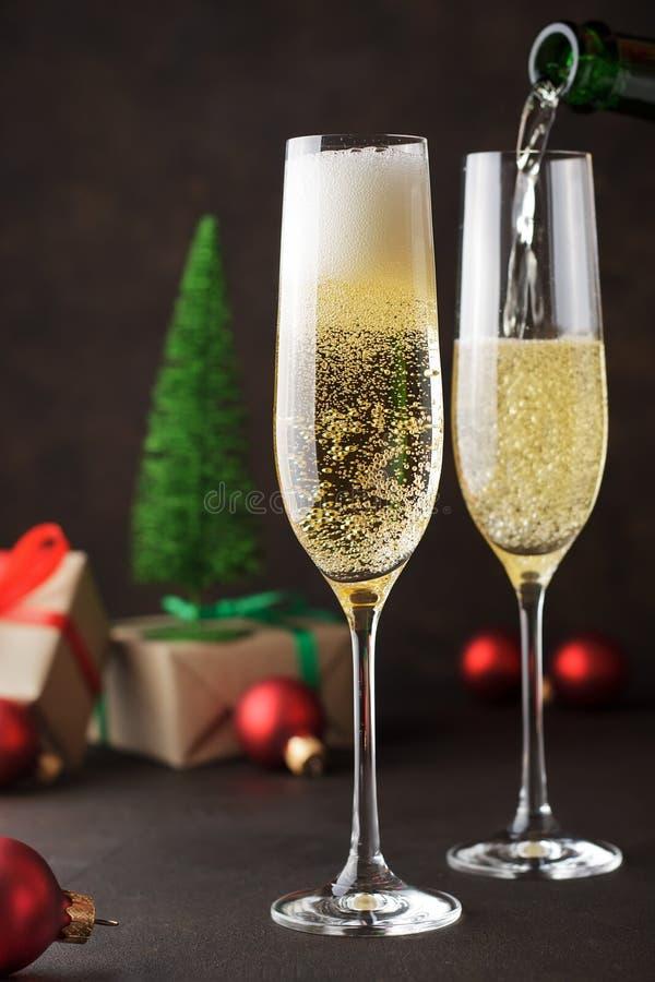 新年` s和圣诞节庆祝的两块香槟玻璃在与礼物和欢乐玩具的黑暗的背景 免版税库存照片