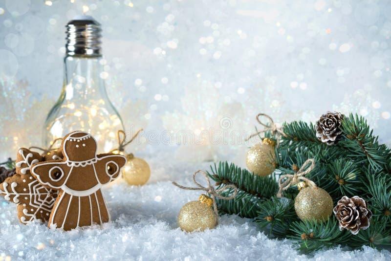 新年` s装饰 与球的圣诞树分支在雪背景和美丽的灯点燃用家庭曲奇饼 免版税库存图片